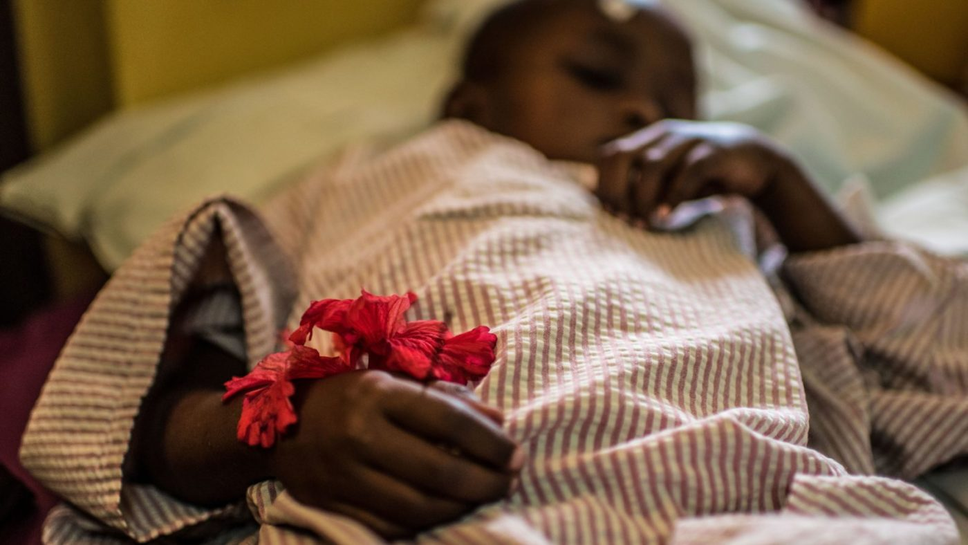 Asha lies in bed waiting for her cataract surgery, clutching a small red flower.