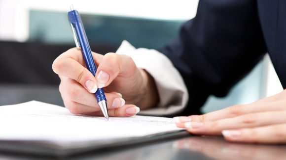 A close-up of a woman's hand holding a pen as she signs a document.