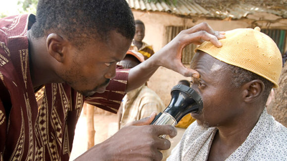 An ophthalmic surgeon carries out an eye examination on a man at an eye clinic in The Gambia.
