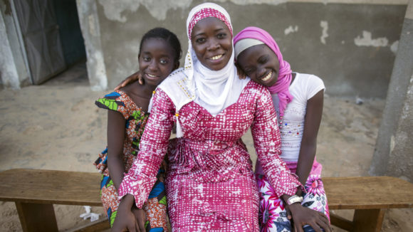 Oumou sits with two children outside on a bench, all three are smiling.