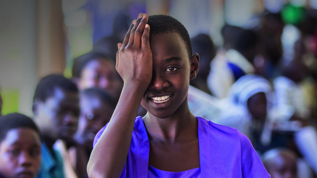 A child is holding one hand across one eye during a screening for eye diseases at Soroti hospital in Uganda as part of the Seeing is Believing project.