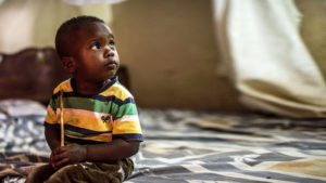 Two year old Bakir Rashid, who suffers from congenital cataracts, sits alone in the bedroom at his home.