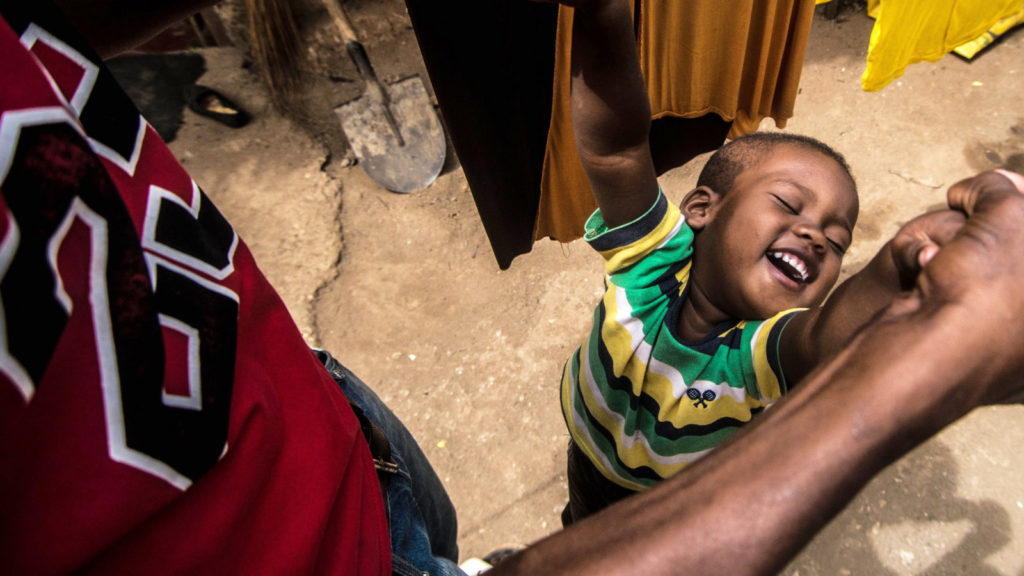 Two-year-old Bakir smiles as he plays with his father.