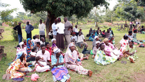 A group of villagers sit on the grass while waiting to be screened for eye conditions at a health centre in Uganda.