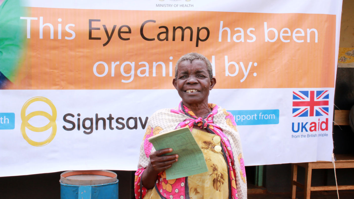 A woman speaks outside a CATCH outreach camp in Uganda about her experience of having cataract surgery to save her sight.