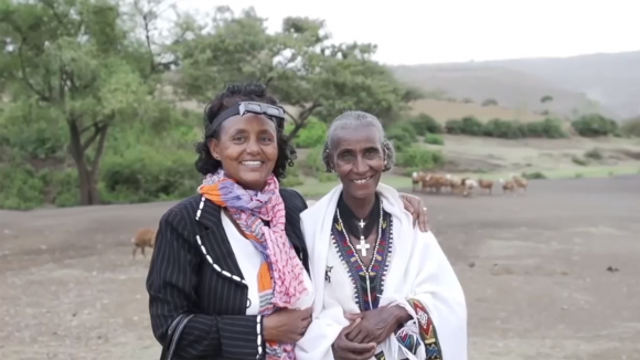 A still from Sightsavers' Global Trachoma Mapping Project video, showing an eye health worker with her arm round a local villager.