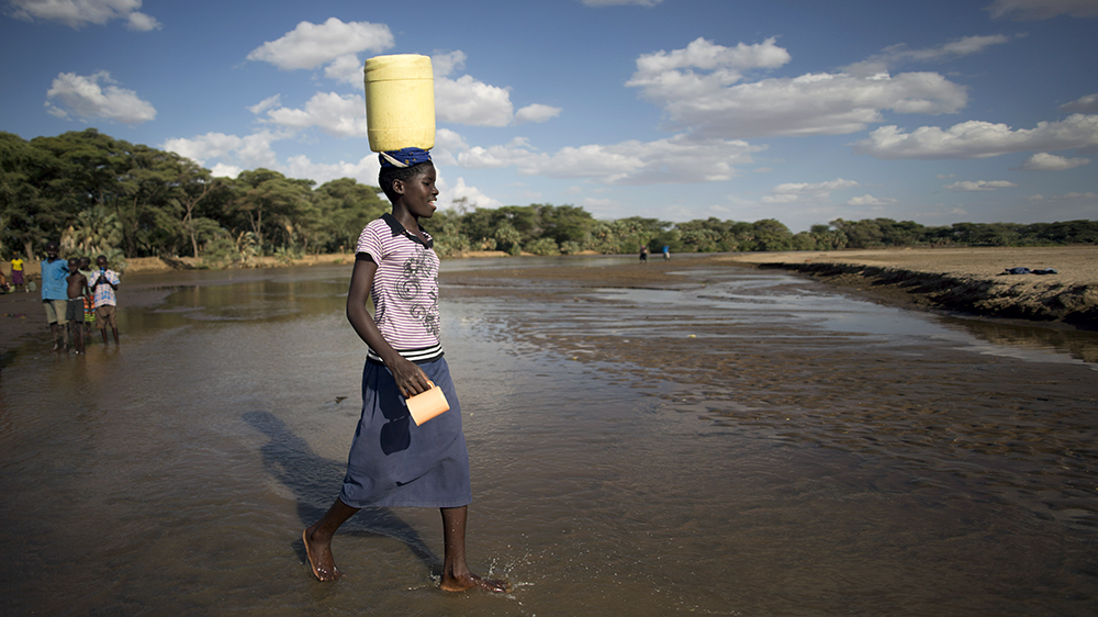 A girl carries water she collected in Turkana, northern Kenya.