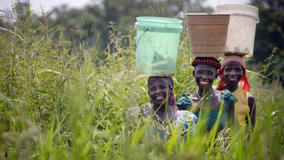 Women carry containers of water on their heads as they return from a river in the village of Garamach in Kaduna, Nigeria.