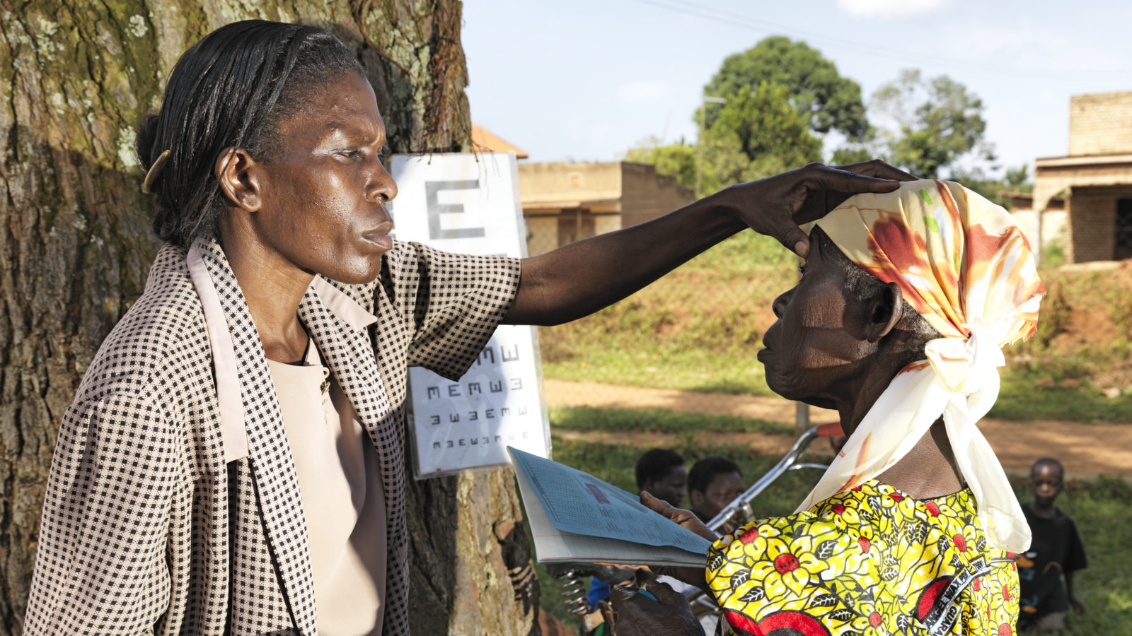 A health worker in Uganda tests a woman's eyes as part of a trachoma outreach camp.