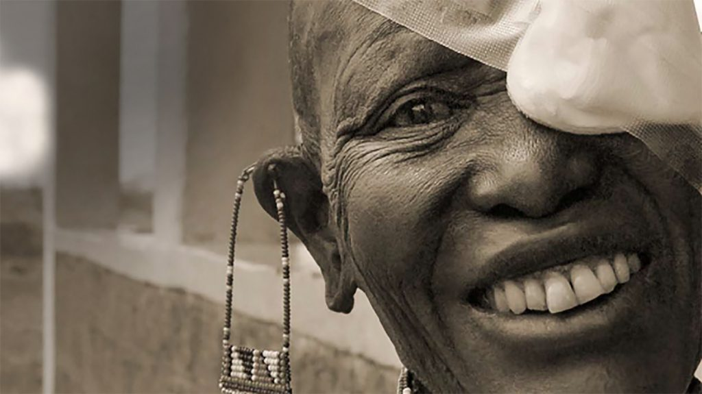 From the cover of Sightsavers annual report 2008: a woman smiles with a bandage across her left eye.
