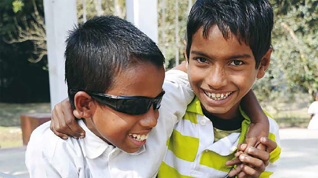 From the cover of Sightsavers annual report 2009: two boys smile with their arms round each other.