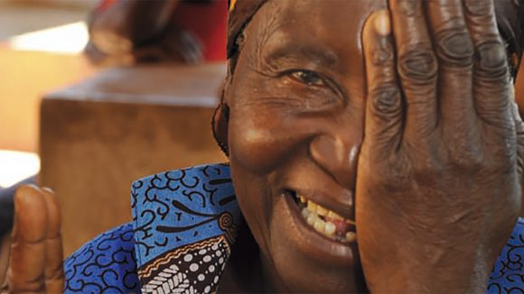 From the cover of Sightsavers annual report 2011: a woman smiling as she covers one of her eyes.
