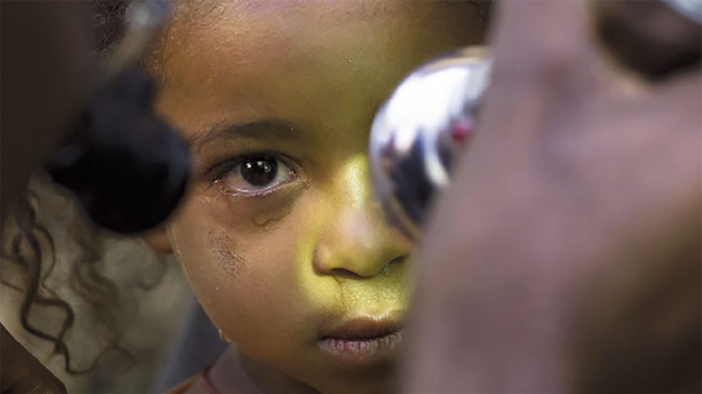 From the cover of Sightsavers annual report 2012: a child having her eyes examined by a doctor.