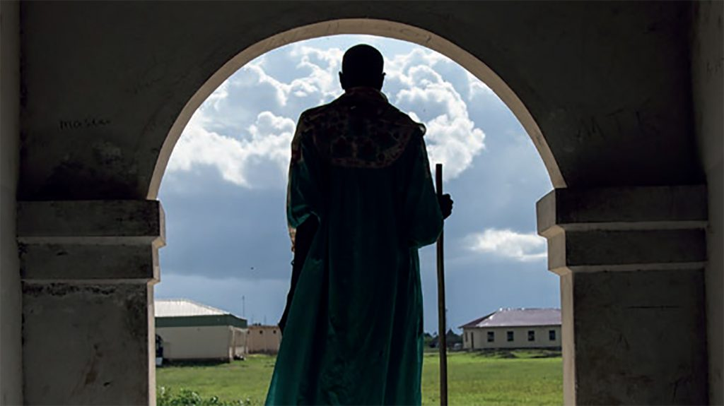 From the cover of Sightsavers annual report 2013: a silhouette of a man standing in a doorway with fields in the background.