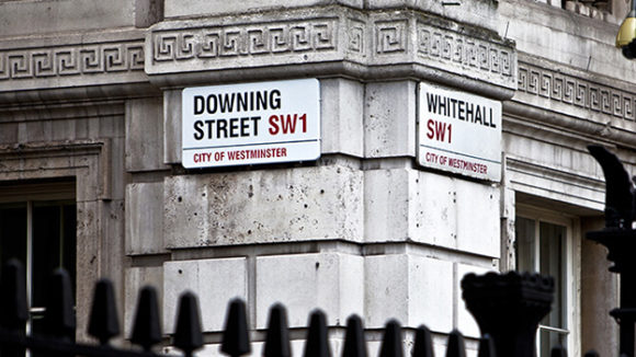 A close-up showing the street signs on Downing Street and Whitehall.