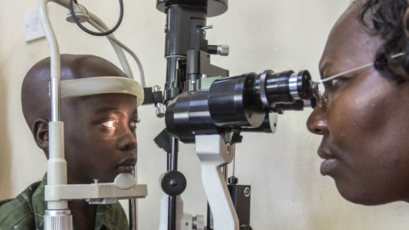 A young boy has his eyes examined by a woman using ophthalmic equipment.