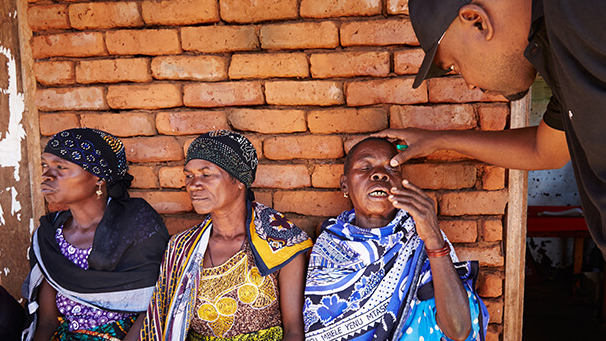 A medical coordin examines patients at an eye health camp in Tanzania.