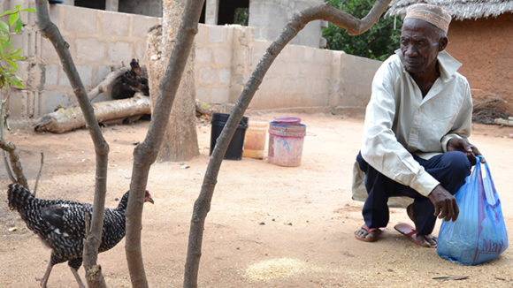 An elderly man crouching down. highlighting the challenges of old age and disability in Tanzania.