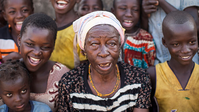 Trachoma patient Amadu Asama from Ghana is surrounded by her grandchildren following her successful operation.