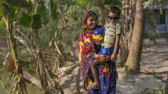 Women in Bangladesh holding her son after his cataract surgery.