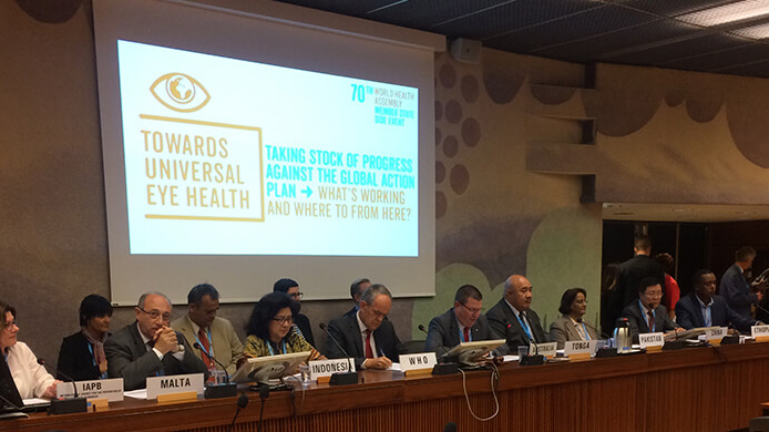 A panel of officials sit in front of a screen at the World Health Assembly.