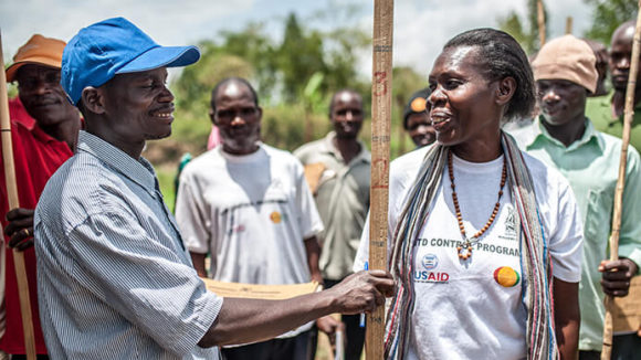 A trainer in Uganda shows a student how to use a measuring stick to calculate drug dosages.