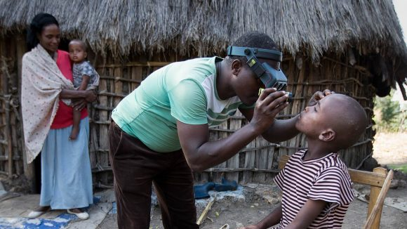 An eye health worker examining a child's eyes.