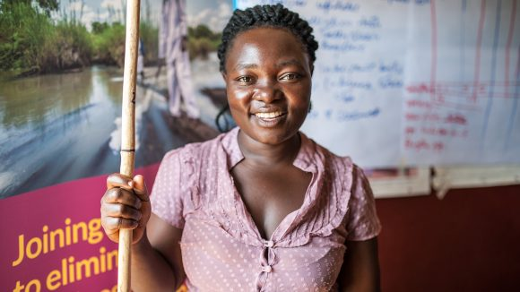 Arjuna Socia, 33 yrs stands inside the Kibwoona Health centre in Masindi, Uganda where she attended the Volunteer Distributor Training for Community Directed Distributors (CDD's) like herself. She is smiling, holding a measuring stick.
