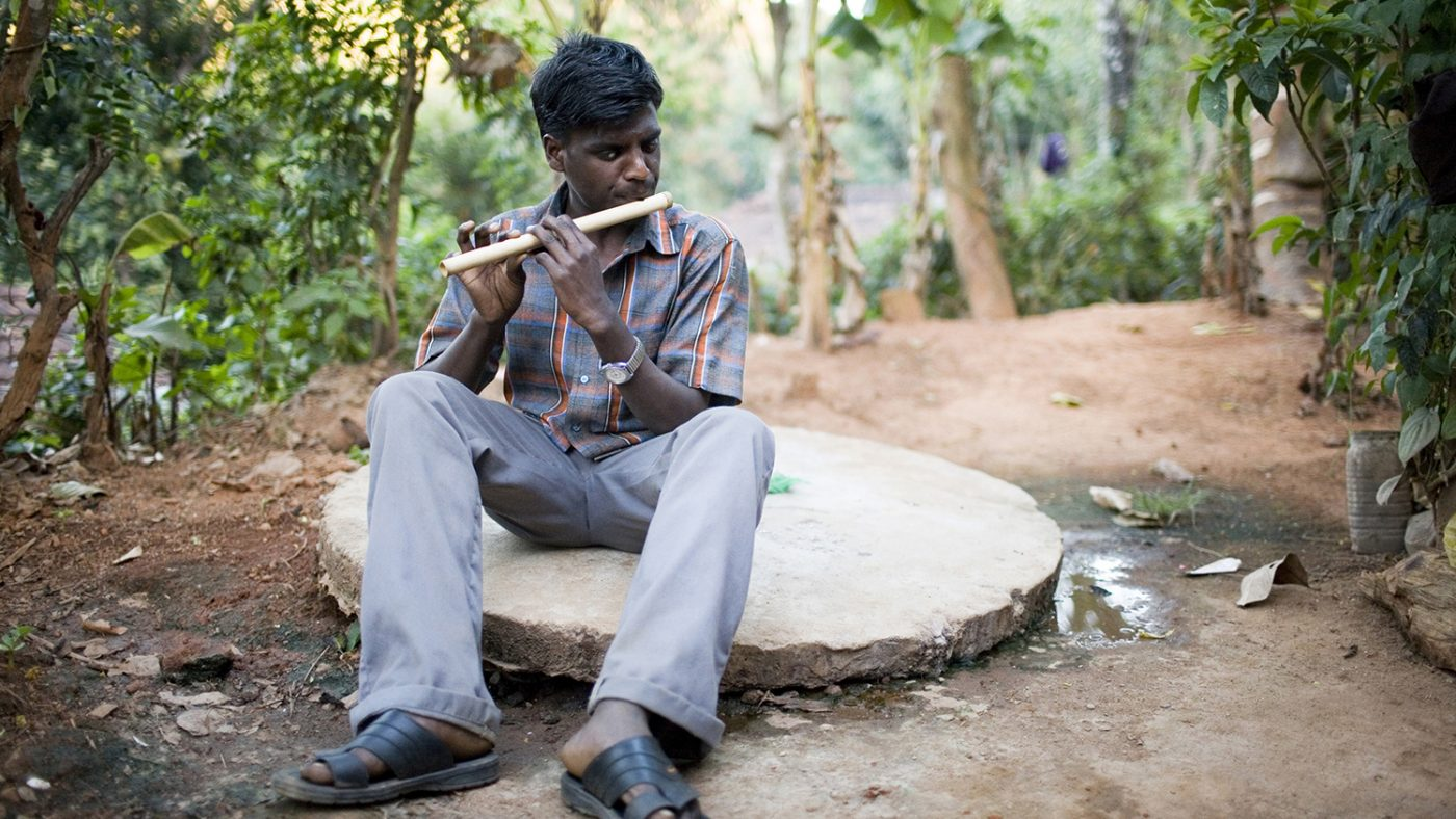 Chandrakumar is sitting on a large stab of concrete playing a flute. Around him are trees.