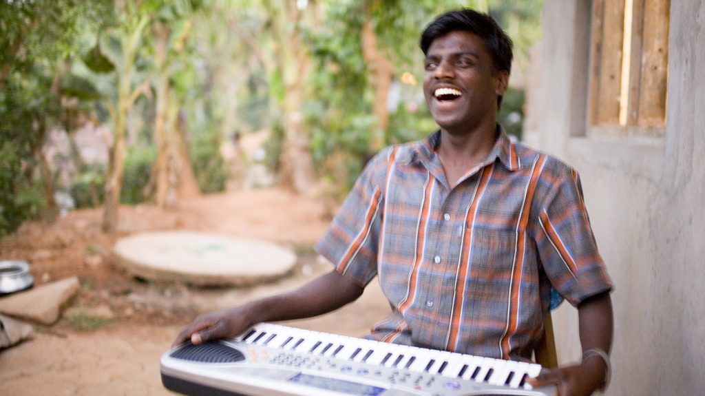 Chandrakumar, who is blind, is sitting down with a musical keyboard on his lap. He is smiling.