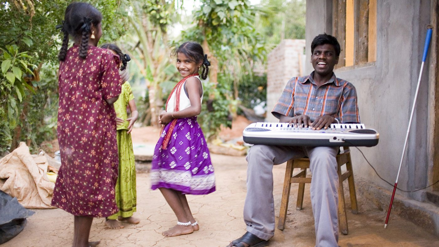 Chandrakumar is sitting down, playing music with 3 children dancing next to him.