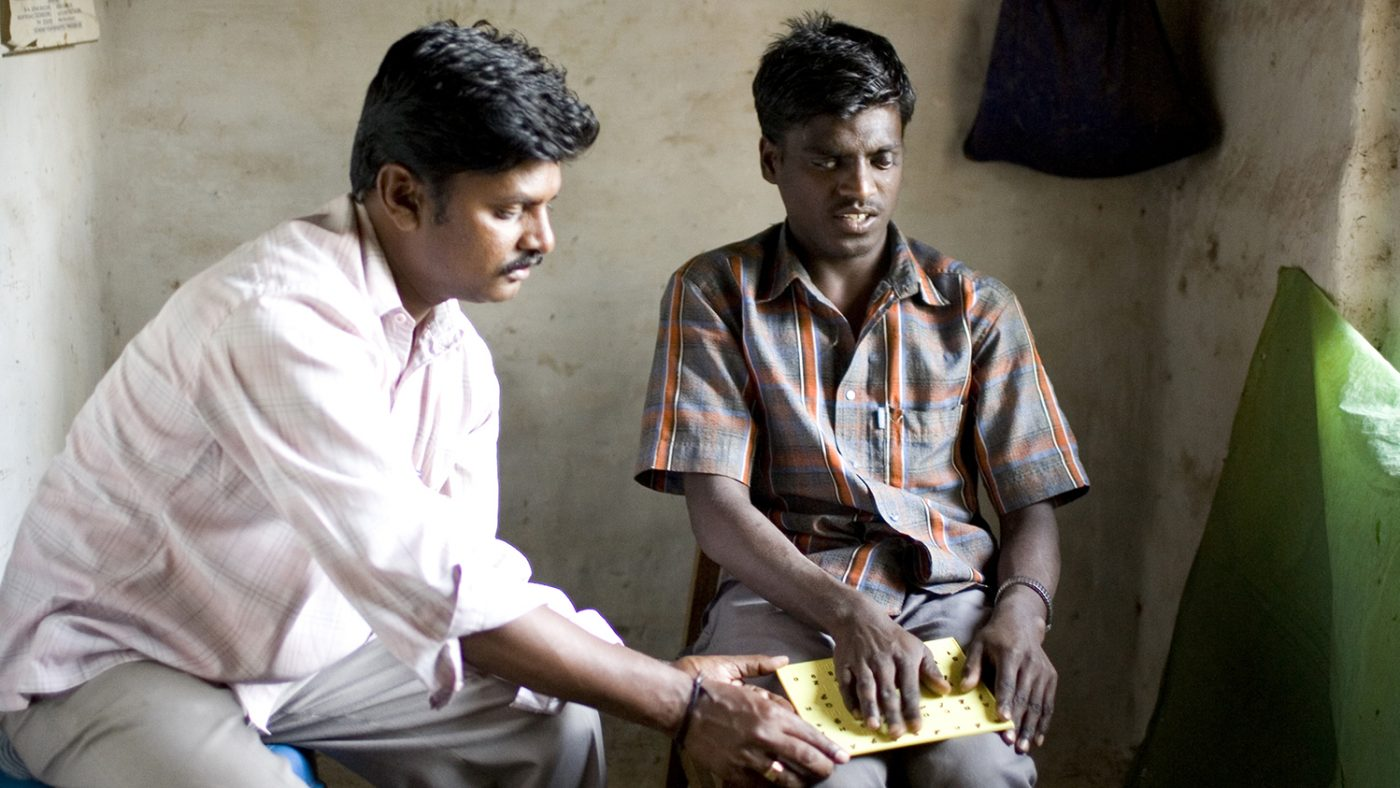 18 year old Chandrakumar, who is blind, reading Braille in his home in India.
