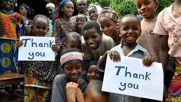 Children hold up signs to say thank you.