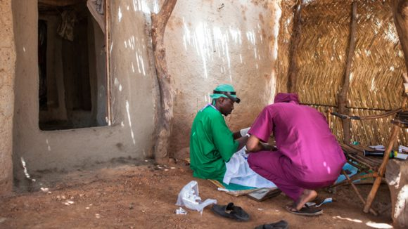 Boubacar Fomba carrying out trachoma surgery on the floor in someone's home.