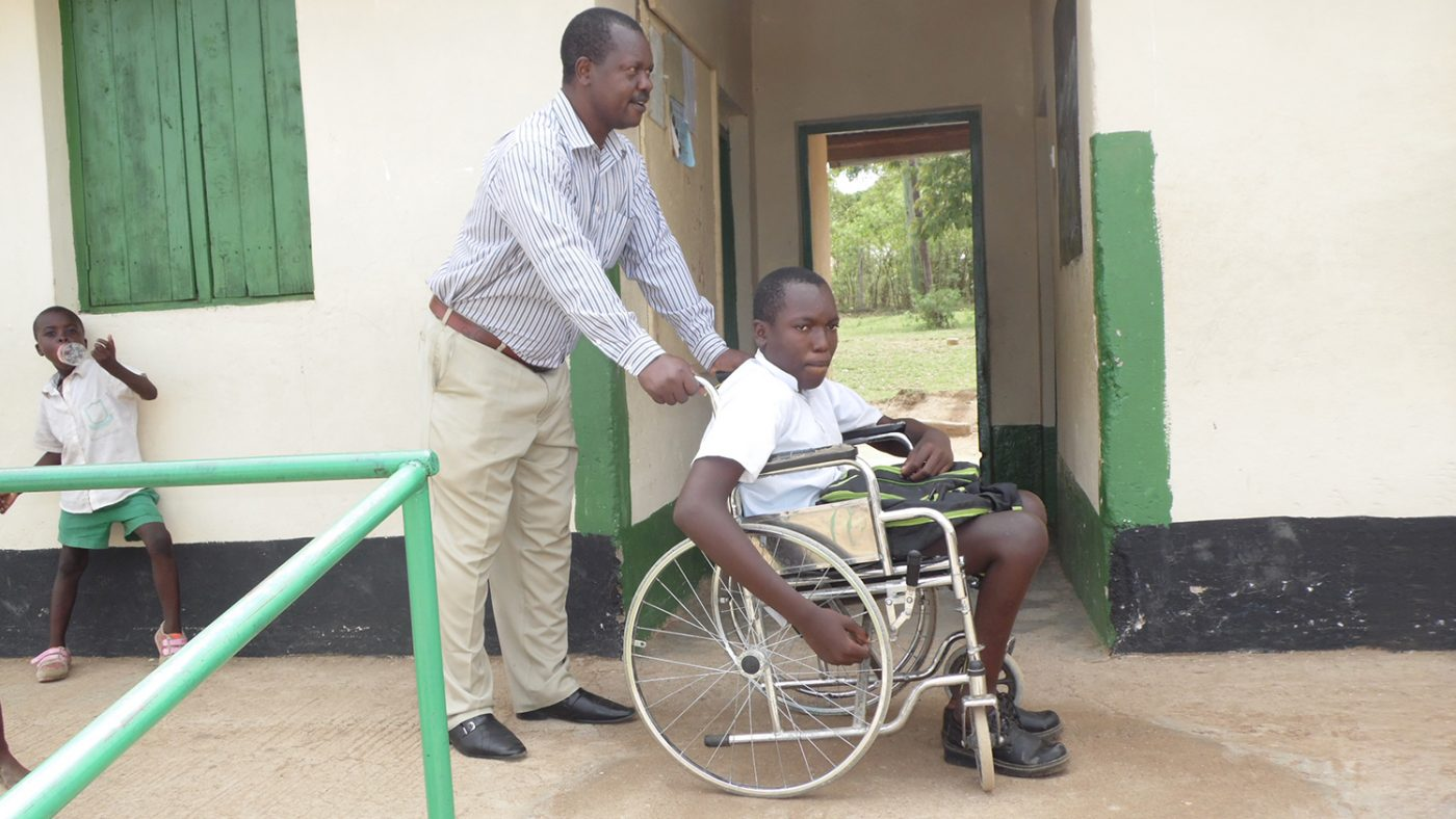 Flash sits in his wheelchair being pushed by a teacher at his school in Kenya.