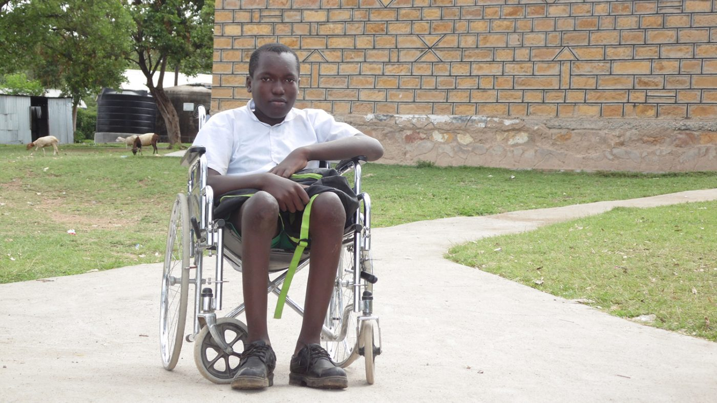 Flash sits in his wheelchair outside his school.