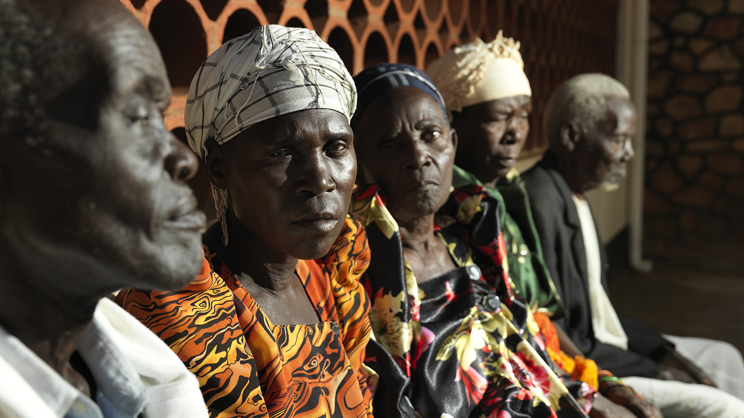 Two men and three women sit next to each other, waiting to have trachoma TT surgery. The two women are looking at the camera.