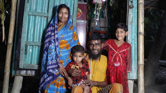 Hazrat stands with a woman and two small boys in front of a small shop in Bangladesh.
