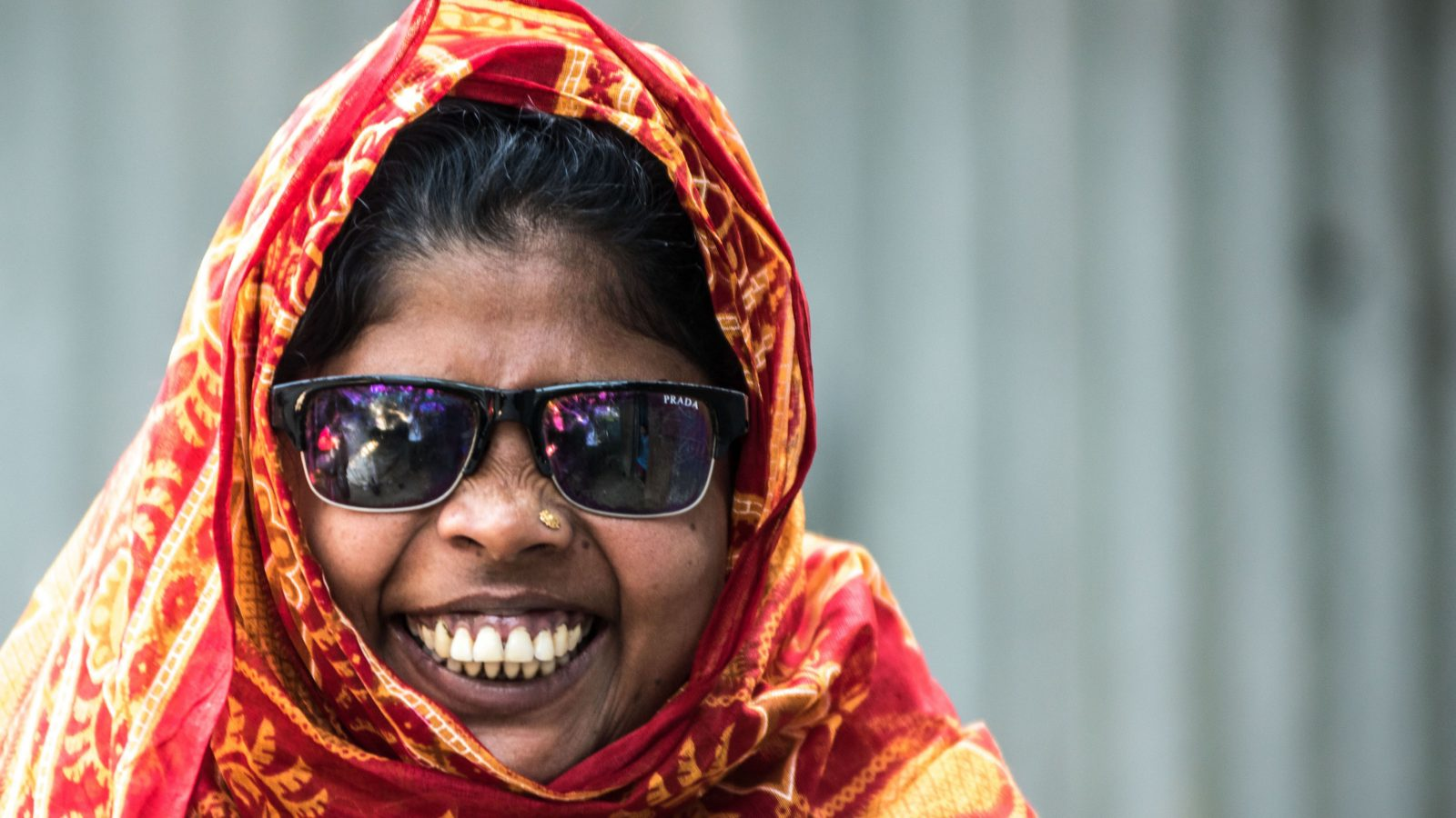 Smiling woman, who is a disability rights activist, wearing sunglasses and orange headscarf.