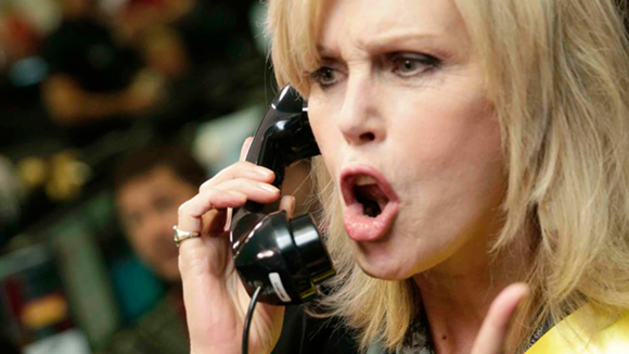 Close up photograph of Joanna Lumley speaking loudly throuugh a telephone.