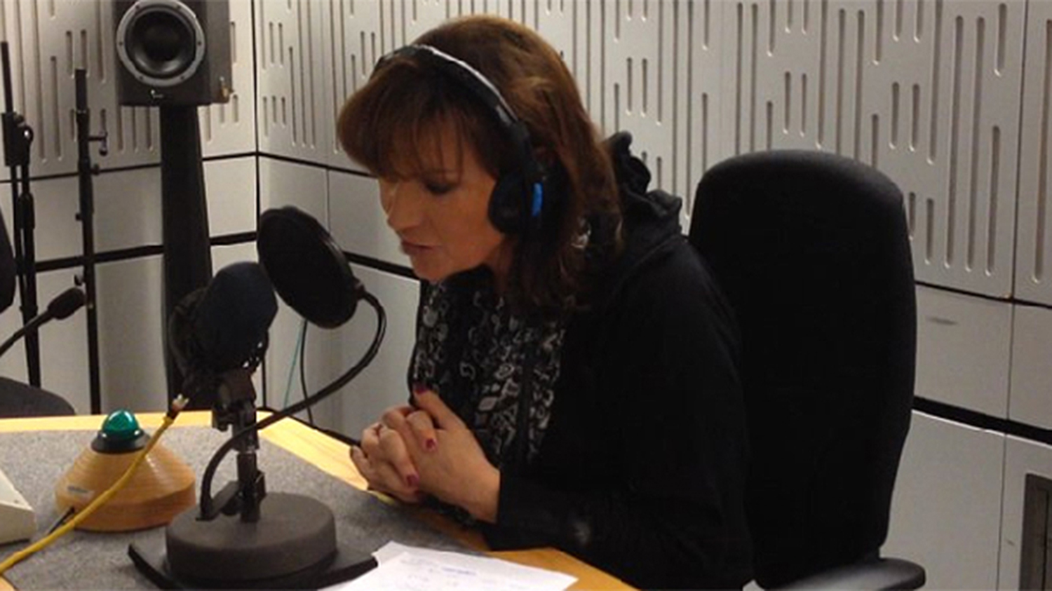 Lorraine leans over and speaks into a microphone. She has headphones on and is wearing a dark top.