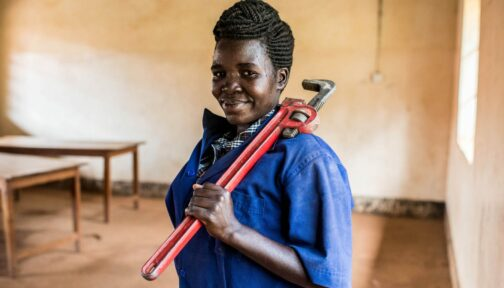 Woman wearing blue worksuit holding red wrench.