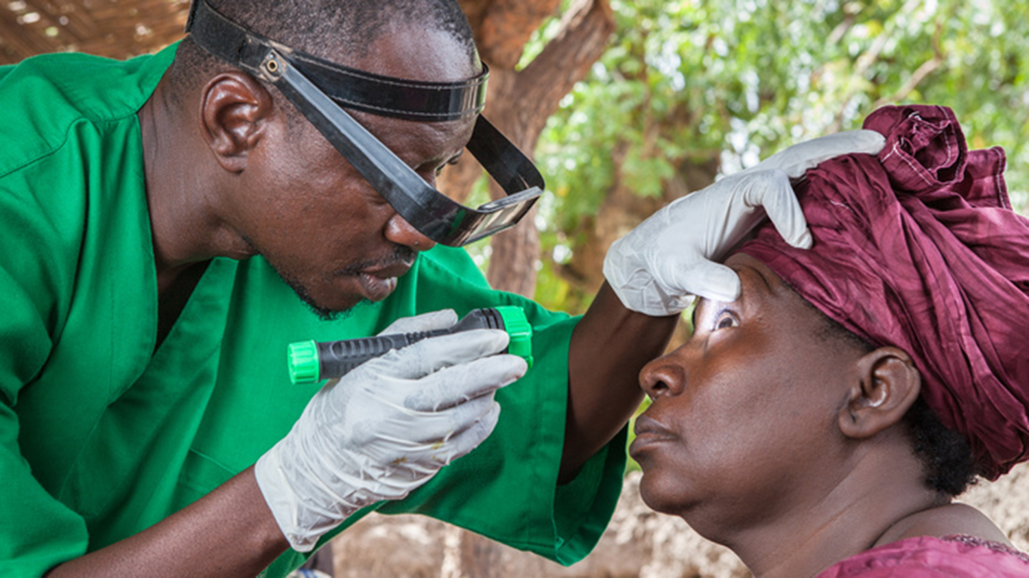 Surgeon, Boubacar Fomb, leans over and examines a lady, Assetou Diakite, using a light, shining into her eye. The surgeon is wearing green and the patient is wearing a matching red top and headscarf.