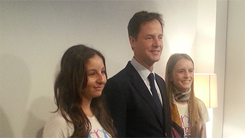 Nick Clegg standing between two teenage girls.