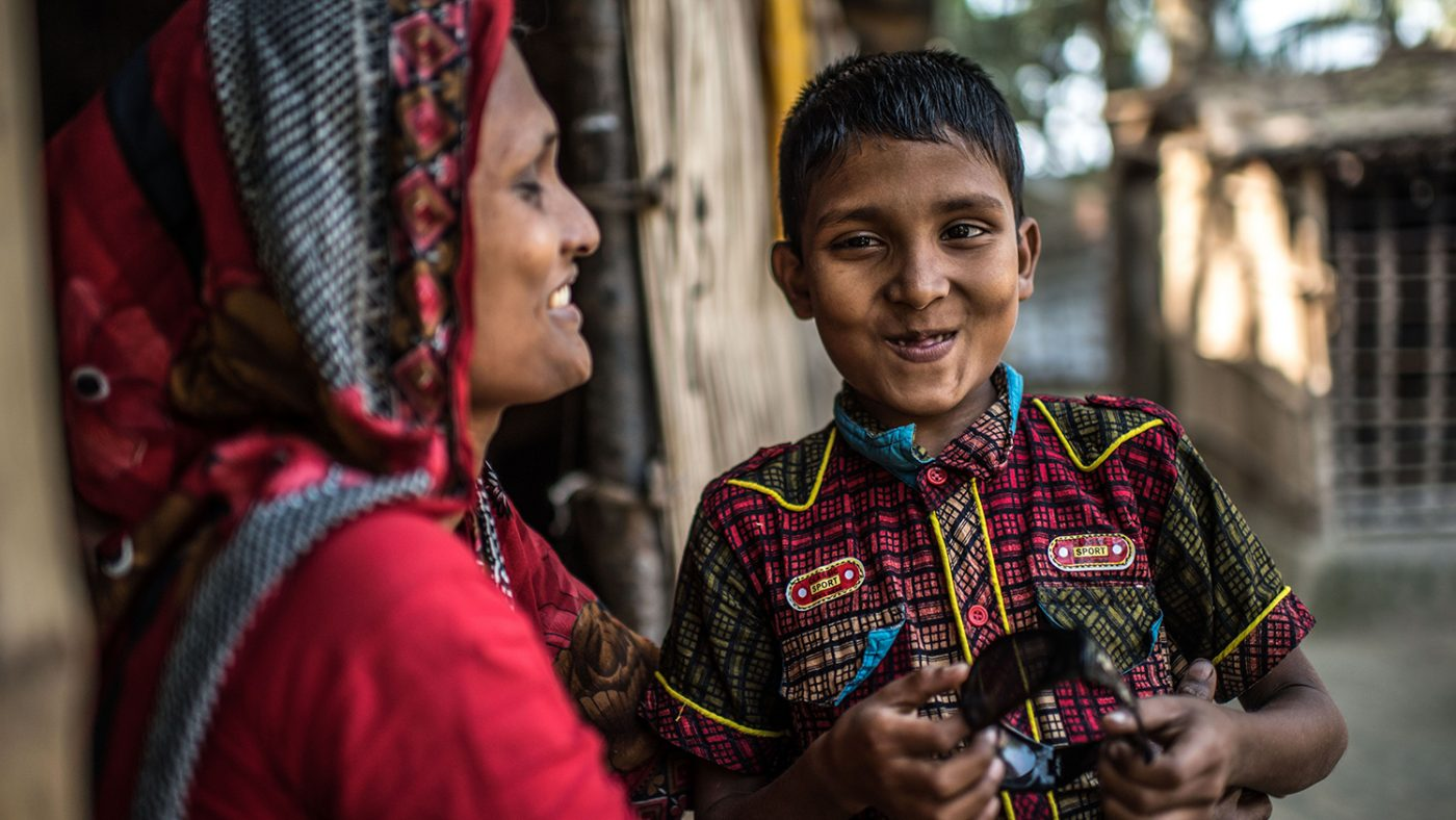 Nine-year-old Polok smiles with his mother at home after undergoing cataract removal surgery.