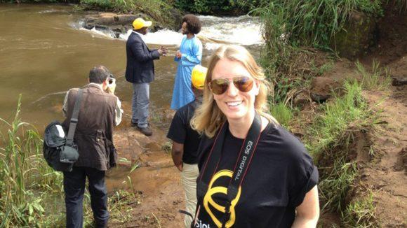 A women wearing a Sightsavers t-shirt stands near a river.