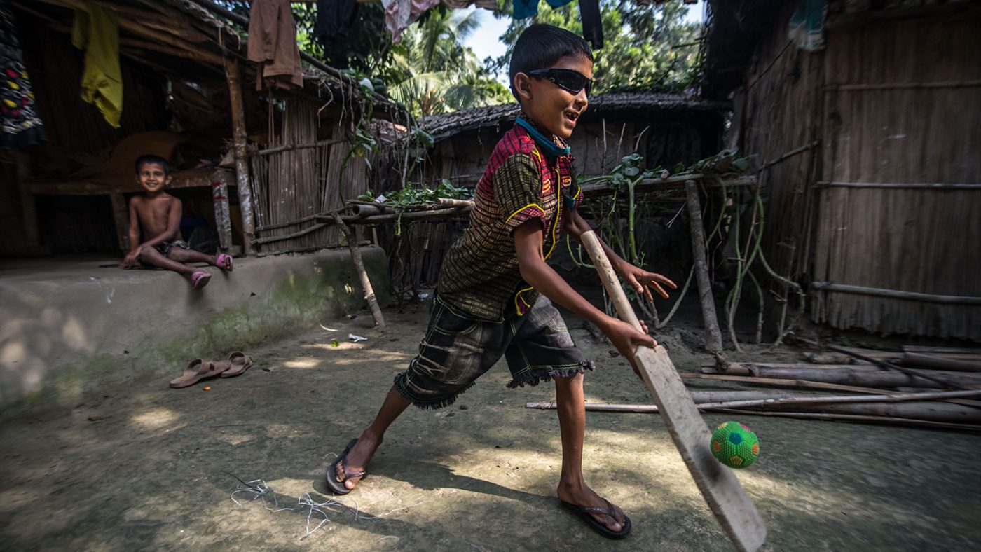 Nine year old Polok Islam plays cricket with his neighbours at home in Salikupa, Bangladesh, days after undergoing cataract removal surgery. He is running with a bat which has just hit a green ball. Polok has black glasses on and is smiling.