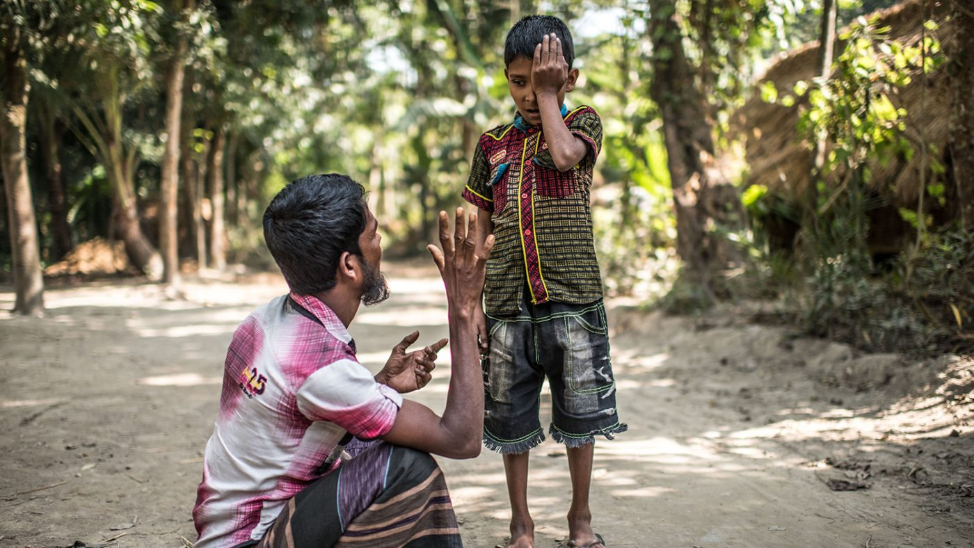 Polok stands and holds one hand over one eye. He looks down at his father who is sitting on the ground, holding up a high five to test Polok's vision.