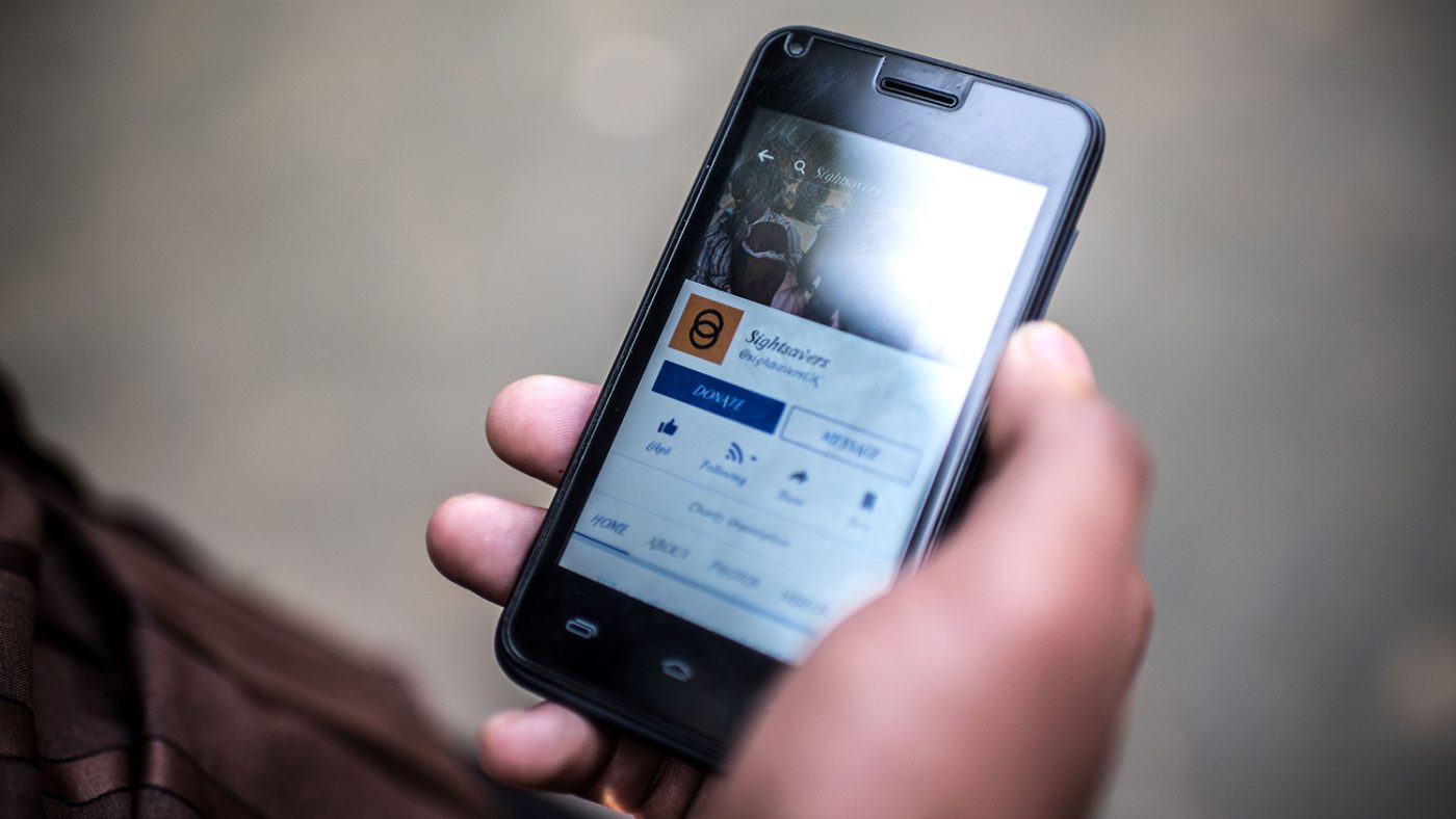 A photo of a phone in Sisan's hand. On the screen is Sightsavers' Facebook page.