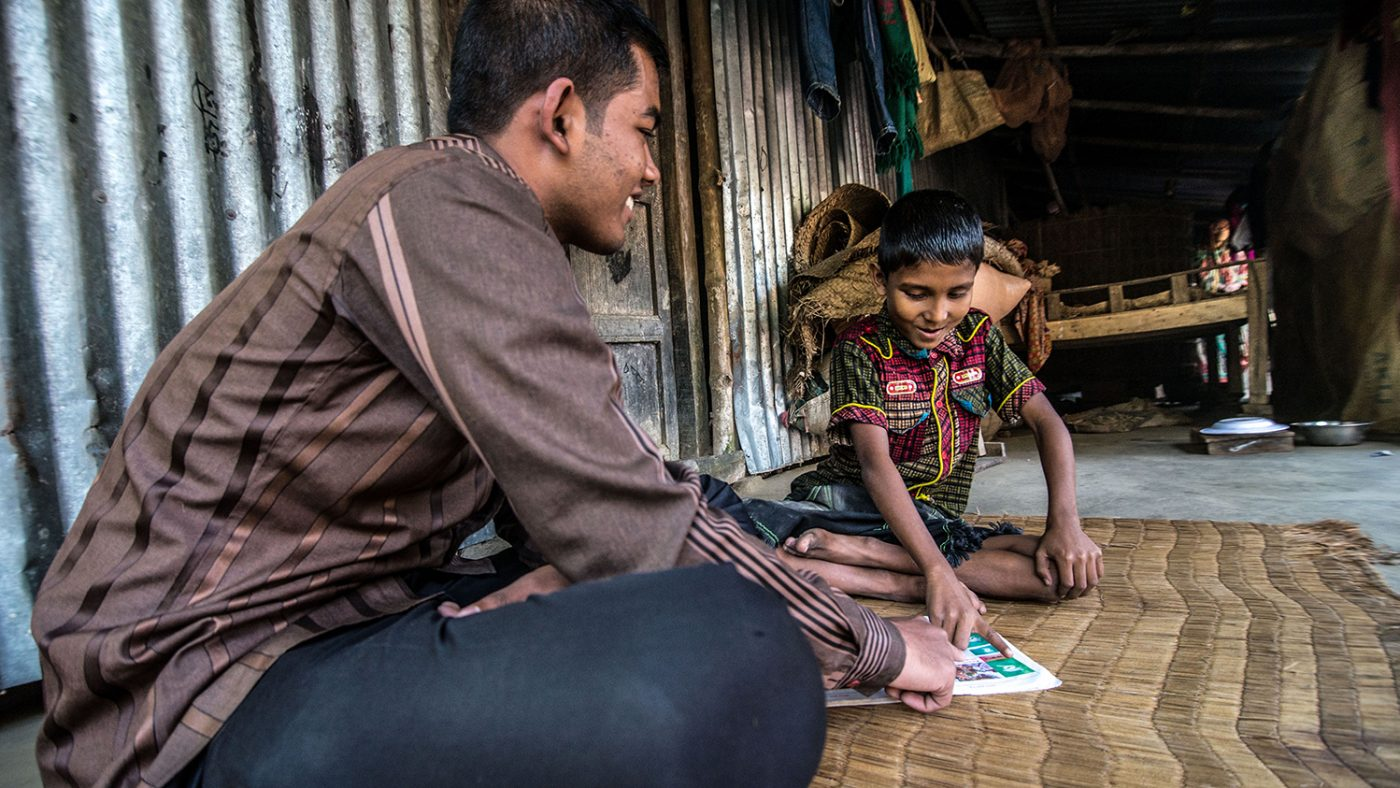 Sisan Hossain teaches his cousin Polok Islam to read, days after Polok underwent cataract removal surgery in Khulna, Bangladesh. They are both sitting on the floor, on a mat. Polok is pointing to a page in a book and both of them are smiling.